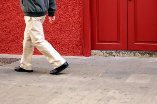 Man walks by red wall.